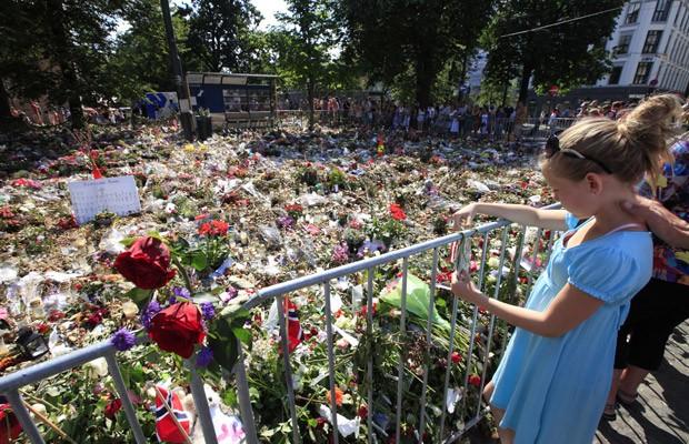 Noruegueses prestam novo tributo às vítimas do atirador, neste domingo (31), nos arredores da Catedral de Oslo (Foto: AP)