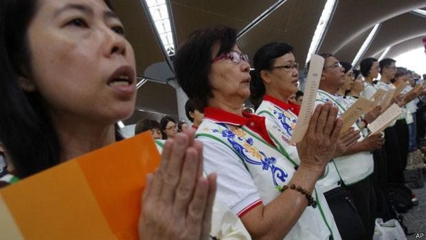 Budistas rezam pelos passageiros do voo desaparecido no aeroporto de Kuala Lumpur (Foto: AP)