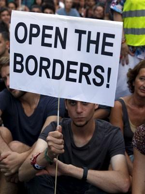 Manifestante em Madri, na Espanha, levanta cartaz a favor da abertura das fronteiras da União Europeia aos refugiados (Foto: Reuters/Susana Vera)