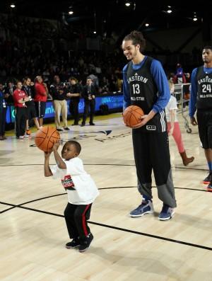 Joakim Noah e criança no treino para o All-Star Game da NBA (Foto: AFP)