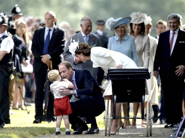 A família dá atenção a George, após o batizado da princesa Charlotte (Foto: AP)