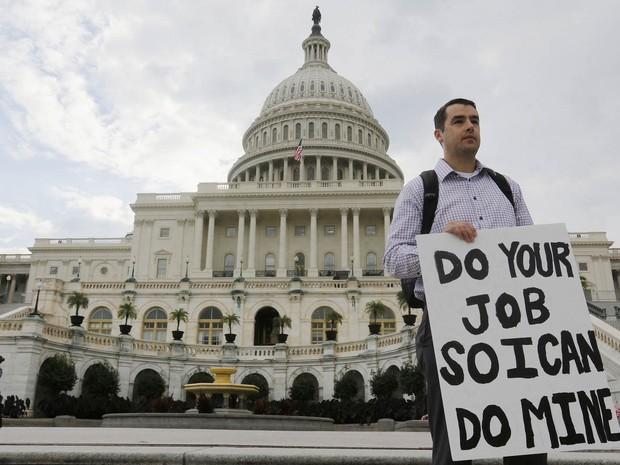 Funcionário mostra cartaz em frente ao Capitólio, em Washington: 'Faça o seu trabalho para que eu possa fazer o meu' (Foto: Larry Downing/Reuters)