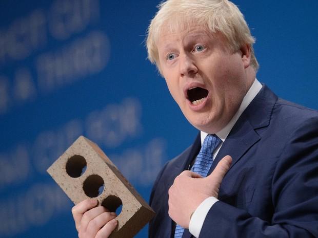 O prefeito de Londres Boris Johnson segura um tijolo enquanto discursa no terceiro dia da conferência anual do Partido Conservador britânico em Birmingham, centro da Inglaterra (Foto: Leon Neal/AFP)