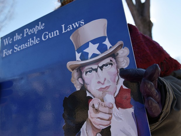 Manifestante exibe cartaz pedindo leis 'sensíveis' sobre armas nos EUA, em Washington, na segunda (4) (Foto: AFP Photo/Mandel Ngan)