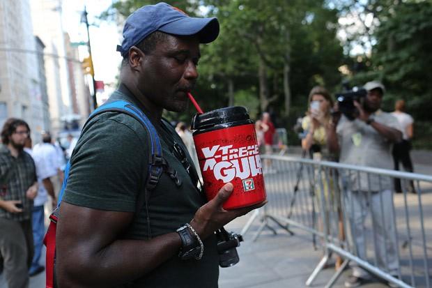 Manifestante toma refrigerante em copo gigante durante a Marcha do Grande Gole (Foto: Spencer Platt / Getty Images / AFP)