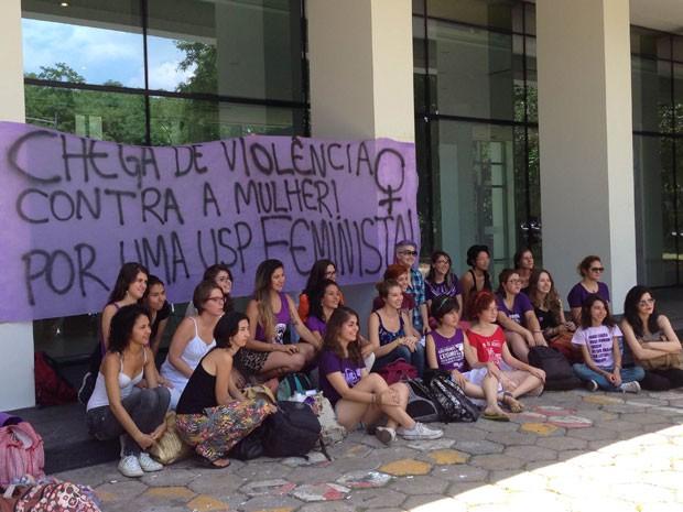 Estudantes posam em frente ao cartaz pedindo o fim da violência contra mulheres na USP (Foto: Ana Carolina Moreno/G1)