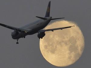 Avião chega para aterrissar no aeroporto de Heathrow, em Londres, com a lua cheia ao fundo. (Foto: Toby Melville/Reuters)