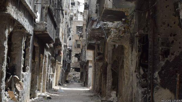 """Campo de Yarmouk, nos arredores de Damasco, onde vários dos ocupantes do prédio viviam na Síria Segundo a ONU, 18 mil pessoas resistem hoje no local """"sob constante ameaça de violência armada, sem condições de acesso a água, comida e serviços básicos de saúde"""" (Foto: BBC)"""