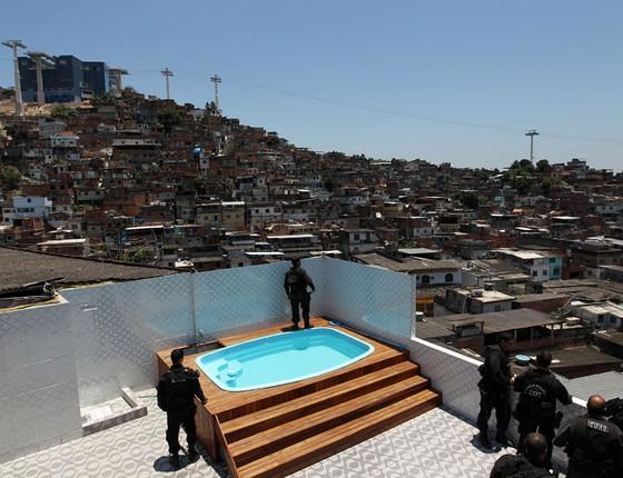 Policiais da Coordenadoria de Recursos Especiais (CORE) observam o morro ao lado da piscina construída na laje da casa do traficante Pezão (Foto: ROBSON FERNANDJES/ESTADÃO CONTEÚDO)