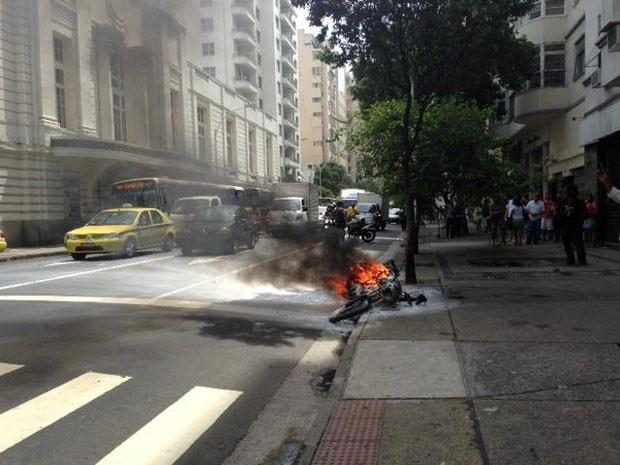 Moto pega fogo na Avenida Nossa Senhora de Copacabana, próximo ao bueiro que explodiu na tarde desta terça-feira (11) (Foto: G1)