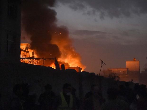 Moradores e forças de segurança observam chama provocada pela explosão de um carro-bomba nesta sexta-feira (1º) no centro de Cabul (Foto: AFP PHOTO/Wakil Kohsar)