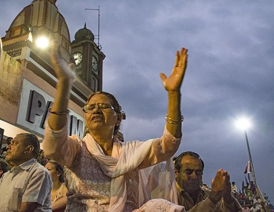 Uma fiel hinduísta acompanha os cânticos religiosos batendo palmas enquanto seu marido faz uma oração de frente ao Ganges (Foto: © Haroldo Castro/Época)