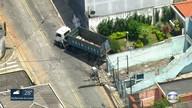 Caminhão sem freio derruba poste, bate em muro de casa