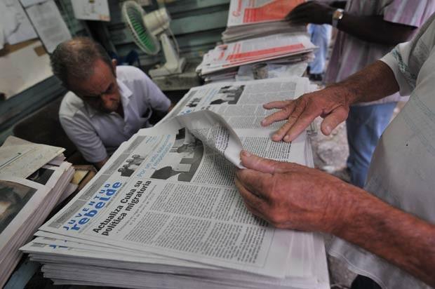 Cubanos leem nesta terça-feira (16) em Havana o noticiário sobre a reforma na imigração (Foto: AFP)