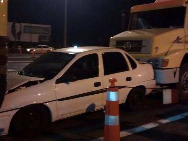 Carro ficou preso entre ônibus e caminhão na praça de pedágio (Foto: Aline Freitas)