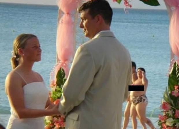 Foto de cerimônia de casamento flagrou, ao fundo, mulher de topless caminhando. (Foto: Reprodução/Oddee.com)