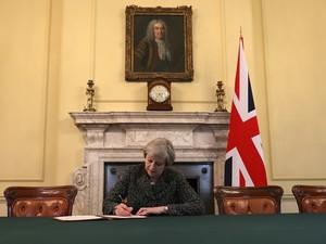 A premiê Theresa May, sentada sob um retrato de Robert Walpole, primeiro a ocupar o cargo de primeiro-ministro em seu país, assina a carta invocando o Artigo 50, para a saída britânica da União Europeia