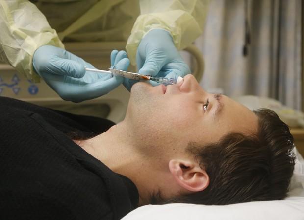 Daniel Bennett, de 26 anos, recebe uma esguichada de vírus da gripe no nariz  (Foto: AP Photo/Charles Dharapak)
