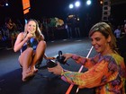 Carla Perez ajuda Claudia Leitte a tirar sandálias em show de Xanddy