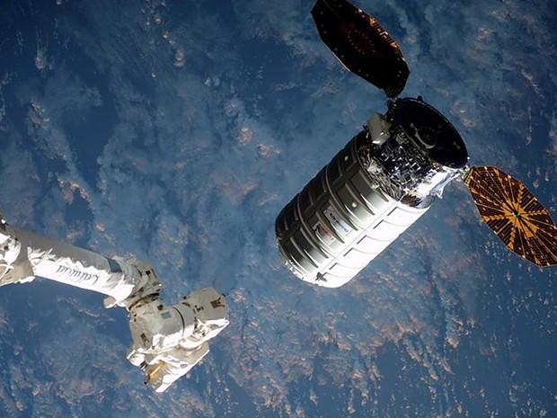 Cápsula Cygnus se aproxima de braço robótico da Estação Espacial Internacional em imagem tirada neste sábado (26)  (Foto: Reuters/Nasa)