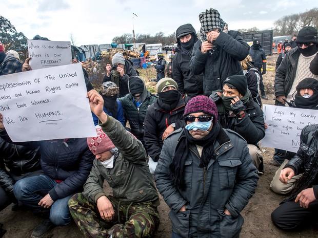 Iranianos protestam com os lábios costurados após terem seu barraco desmontado no campo de Calais, na França (Foto: Philippe Huguen/AFP)