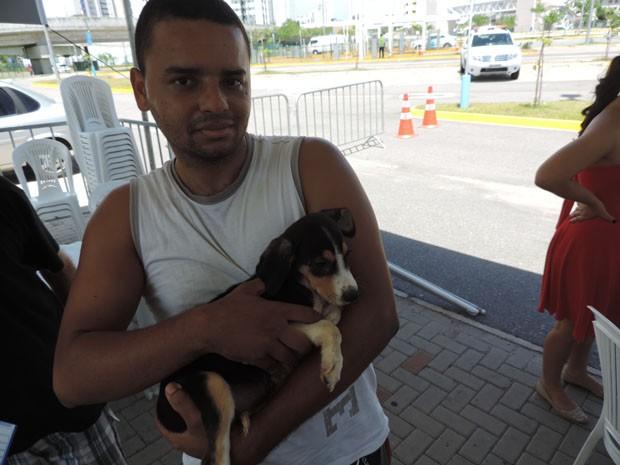 Pedro Edson se comoveu com a história dos cachorros abandonados e acabou levando um dos filhotes que estavam na feira (Foto: Katherine Coutinho/G1)
