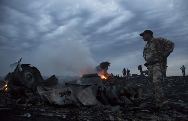 Oficiais observam os destroços do avião da Malaysia Airlines que caiu perto no leste da Ucrânia. A aeronave seguia de Amsterdã para Kuala Lumpur (Foto: AP Photo/Dmitry Lovetsky)