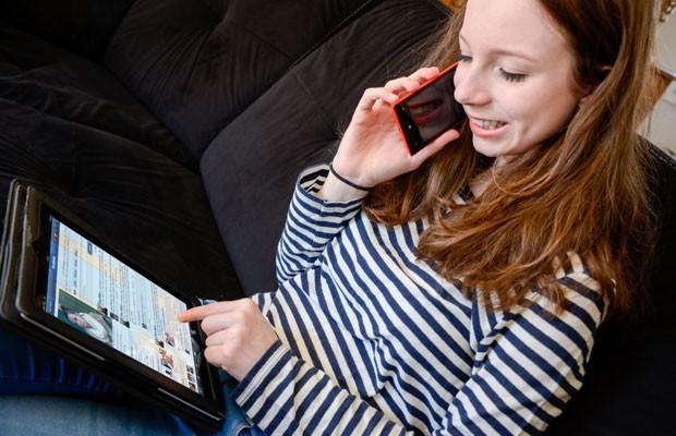 Adolescente usa tablet para acessar internet enquanto fala ao celular.  (Foto:  AJ PHOTO/ BSIP/ AFP)