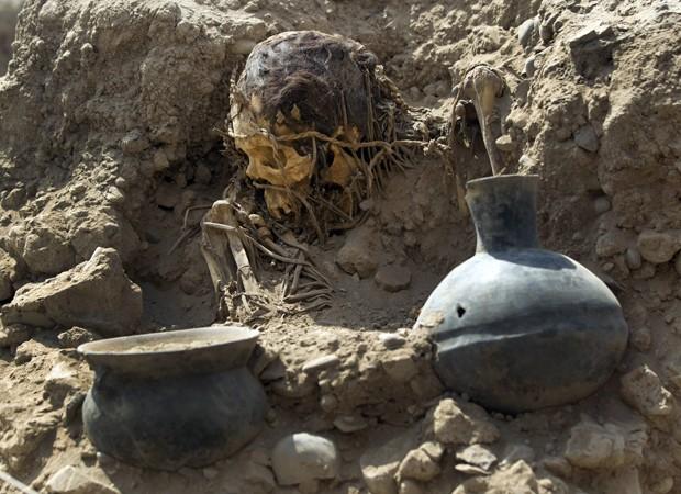 Crânio e objetos encontrados por arqueólogos em complexo esportivo no Peru (Foto: Martin Mejia/AP)