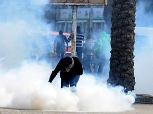 Um manifestante está envolto em gás lacrimogêneo disparados pela polícia para dispersar uma manifestação em Alexandria, Egito. (Foto: Heba Khamis/AP)