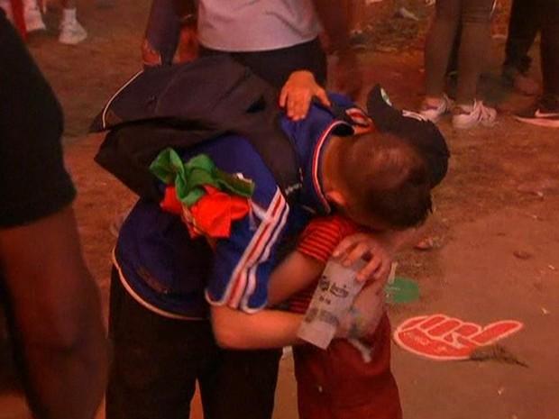 Menino português consola torcedor francês após a final da Eurocopa deste domingo (10) (Foto: Reprodução/BBC)