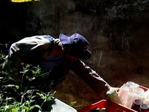 Agente procura focos acumulados em imóvel (Foto: TV Integração/Reprodução)