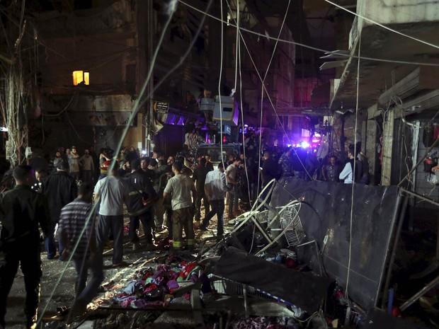 Moradores observam área danificada por explosões no sul de Beirute, no Líbano. Dezenas de pessoas foram mortas por ataques suicidas simultâneos em local movimentado do subúrbio da capital, onde há a presença do Hezbollah libanês (Foto: Hasan Shaaban/Reuters)