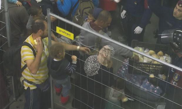 Entre a multidão estão mulheres e crianças, que tentam segurar os sanduíches jogados no local, enquanto as pessoas que estão mais ao fundo tentam chamar a atenção das pessoas que distribuem comida. (Foto: Reprodução/YouTube/Sprido08)