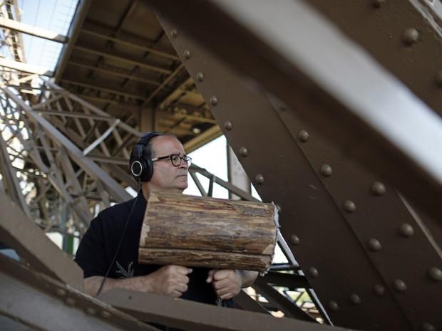 O compositor Joseph Bertolozzi usa tábua de madeira para fazer música com sons da Torre Eiffel, em Paris (Foto: Reuters/Benoit Tessier)