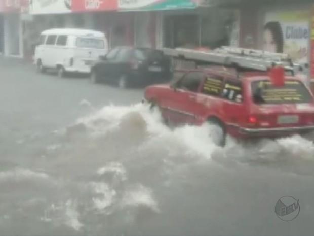 Carro tenta passar por rua alagada no centro de São Joaquim da Barra, SP (Foto: Reprodução/EPTV)