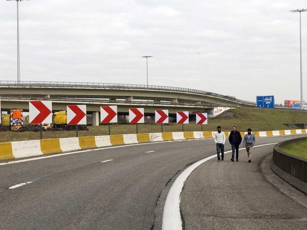Pessoas andam em estrada de acesso ao Aeroporto de Zaventem bloqueada (Foto: Thierry Monasse / AFP Photo)