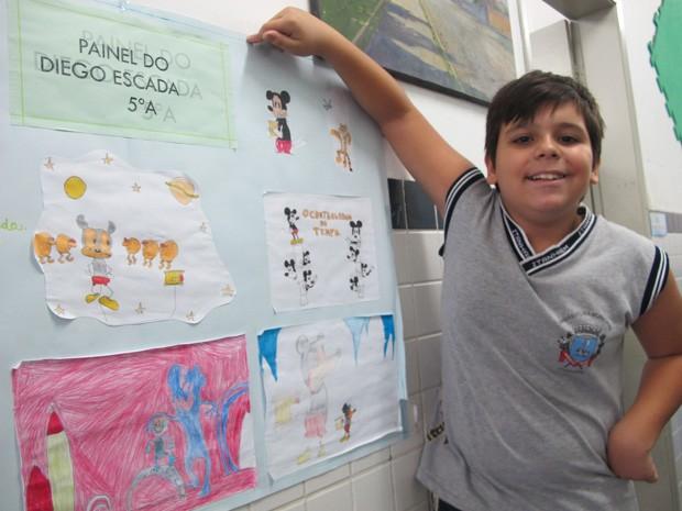 Diego mostra os desenhos que utiliza para contar histórias para a classe  (Foto: Mariane Rossi/G1)