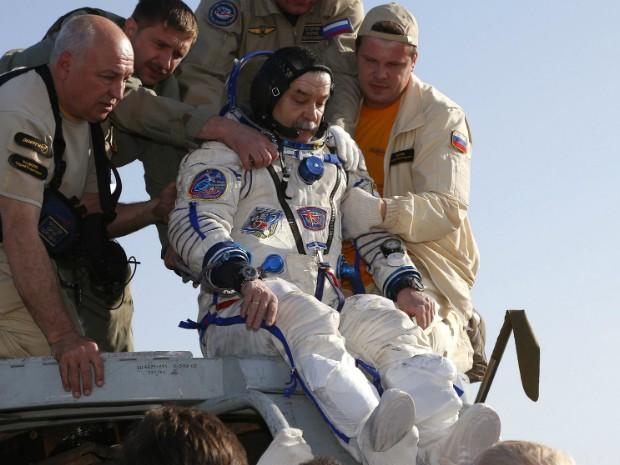 Membro da tripulação, o cosmonauta russo Mikhail Tyurin é ajudado após o desembarque no Cazaquistão (Foto: Dmitry Lovetsky/Pool/Reuters)