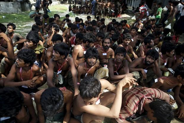 Imigrantes que foram achados em barco no litoral de Mianmar desembarcam após passarem dias na embarcação nesta quarta-feira (3) (Foto: Soe Zeya Tun/Reuters)