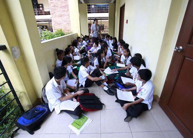 FILIPINAS: Alunos do 9º ano têm aula de 'educação de valores' em um corredor da escola Timoteo Paez, na região metropolitana da Manila. Segundo a professora Kristine Passag, a escola está em reforma por causa da falta de salas de aula (Foto: Reuters/Romeo Ranoco)