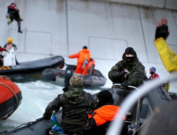 Membro da guarda costeira russa mascarado aponta arma para ativista do Greenpeace. (Foto: AFP Photo/Greenpeace/Denis Sinyakov)