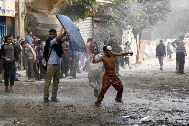 Manifestantes egípcios enfrentam a polícia nesta quinta-feira (22) no Cairo; eles foram às ruas para lembrar os confrontos que, há um ano, mataram 45 manifestantes que pediam mais pressa na transição democrática (Foto: AP)