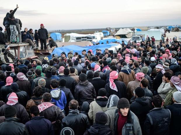 Sírios que saíram da cidade de Aleppo esperam nesta sexta-feira (5) em Bab-Al Salama, perto da cidade Azaz, no norte da Síria, para entrar na Turquia (Foto: BULENT KILIC / AFP)