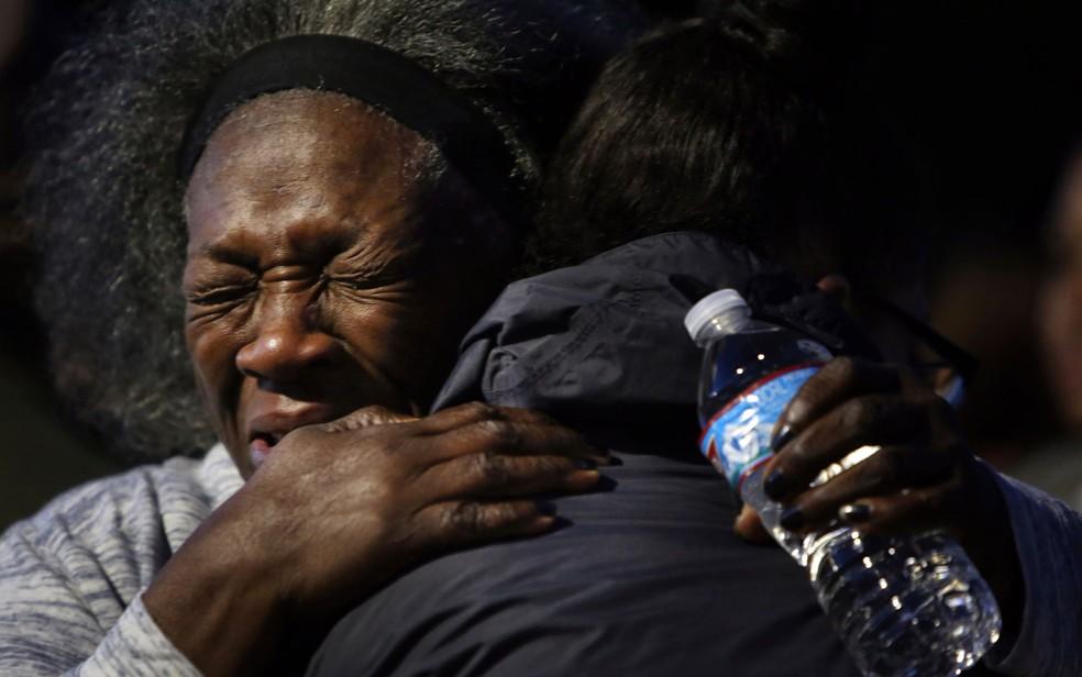 Laurie Davis, tia de Charleena Lyles, abraça outro membro da família durante vigília do lado de fora do prédio onde a sobrinha morava e foi morta por policiais no domingo (18), em Seattle (Foto: Genna Martin/seattlepi.com via AP)