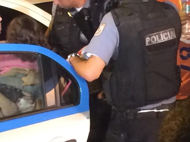 A mãe do bebê que foi levado conversa com policiais na porta da delegacia (Foto: Daniel Silveira/G1)