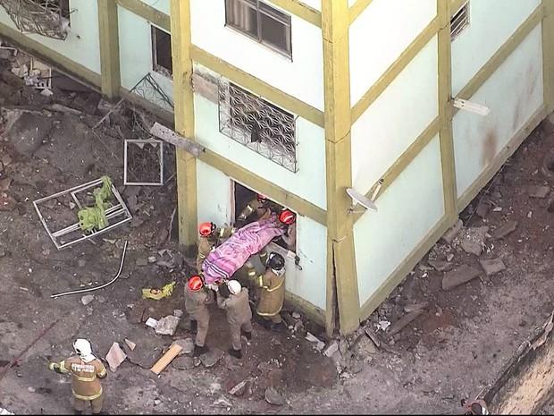 Bombeiros retiram o corpo de uma vítima da explosão na Fazenda Botafogo, no subúrbio do RIo de Janeiro (Foto: Reprodução/TV Globo)