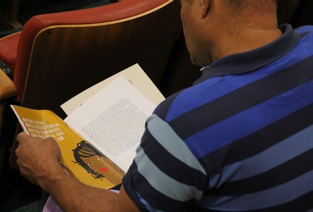 """Participante do curso """"Tempo de Despertar"""" folheia cartilha com conteúdo sobre violência doméstica (Foto: Elisa Gargiulo / MP-SP)"""