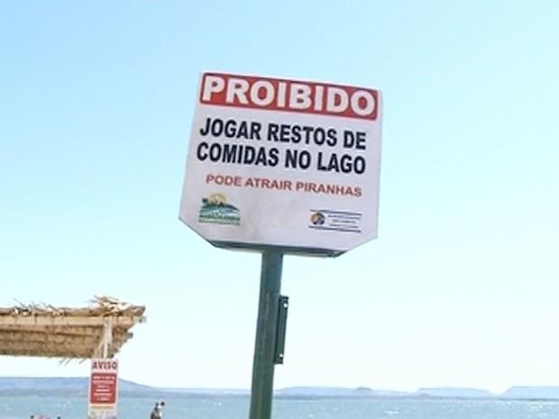 Placa alerta para o risco de piranhas nas águas da praia (Foto: Reprodução/TV Anhanguera)