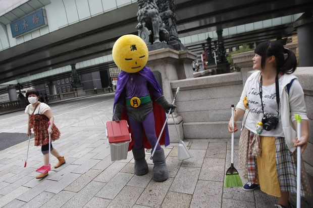 'Lua Cheia' prefere carregar uma vassoura e pá enquanto lidera voluntários na limpeza de áreas na capital japonesa (Foto: Issei Kato/Reuters)